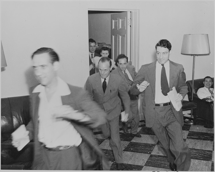 Photograph of reporters rushing excitedly through the White House with news of the Japanese surrender. - NARA - 199172
