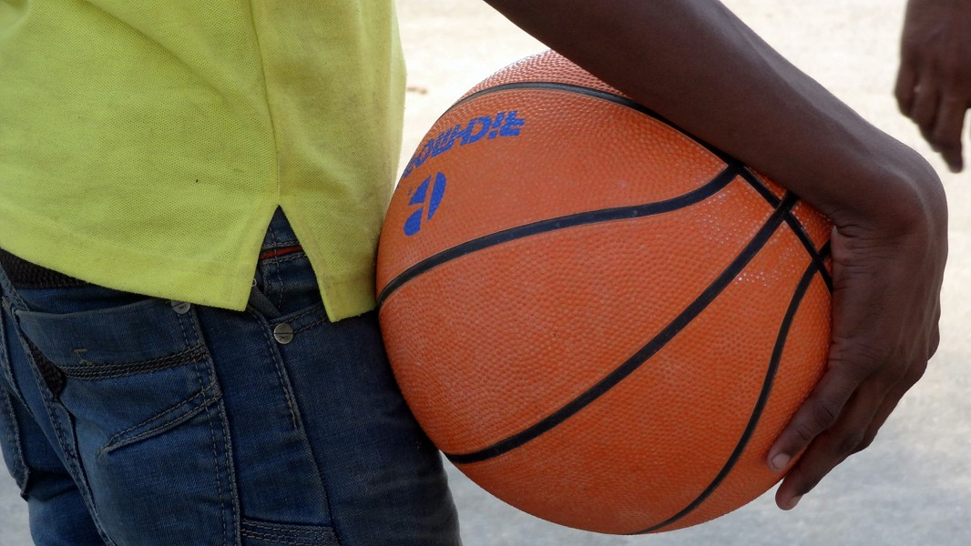 A person holding basket ball in his hand