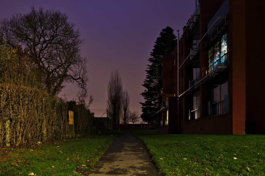 Path leading to the back of a residential appartment building North of Rue Jean Ekelmans in Auderghem, Belgium (evening nautical twilight)
