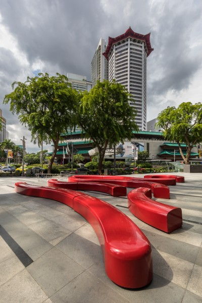 Red curved benches with Angsana trees near the Singapore Marriott Tang Plaza tower