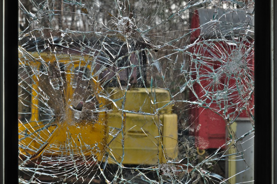 View through the shattered glass of a door in the SNCB B22490 type-K3 carriage, looking at a yellow H. Weyhausen KG backhoe loader in As, Belgium (DSCF3088-hdr)