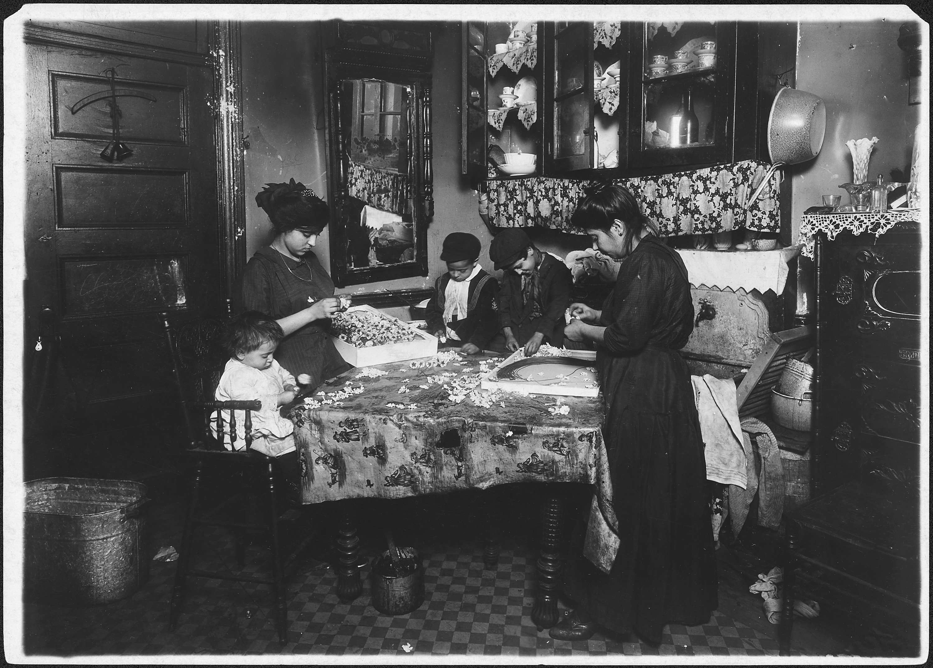 Family of Mrs. Motto making flowers in a dirty tenement. Josephine, 13 years, helps outside of school hours until 9... - NARA - 523495