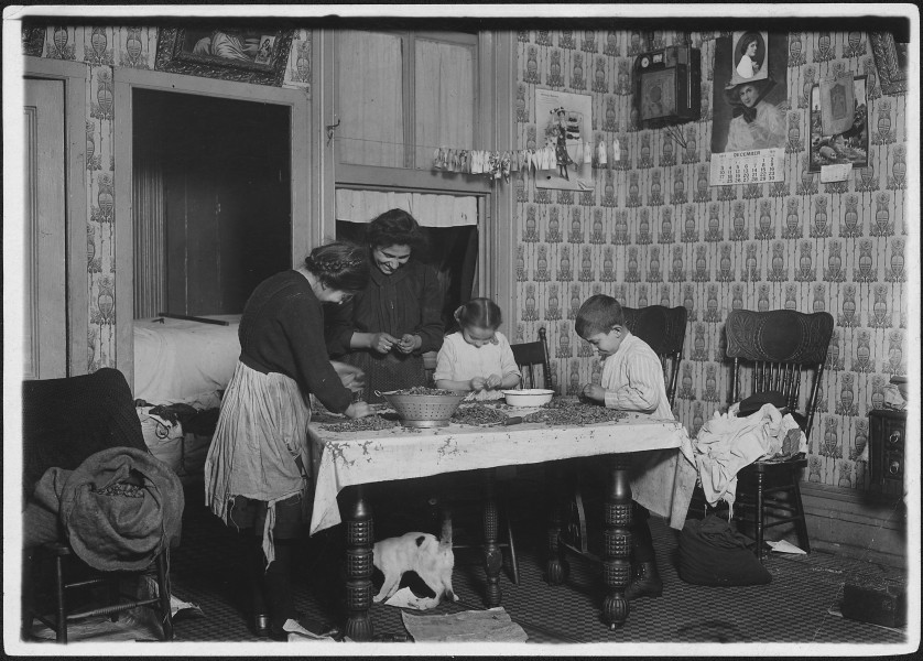 Mrs. Salvia, Joe, 10 years old, Josephine, 14 years, Camille, 7 years, picking nuts in a dirty tenement home. The bag... - NARA - 523490