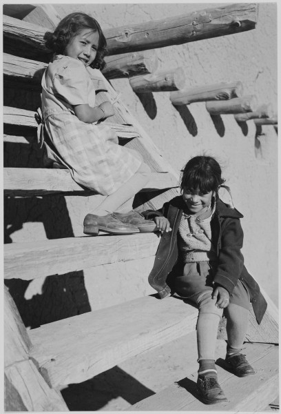Two young girls sitting on steps. At San Ildefonso Pueblo, New Mexico, 1942.