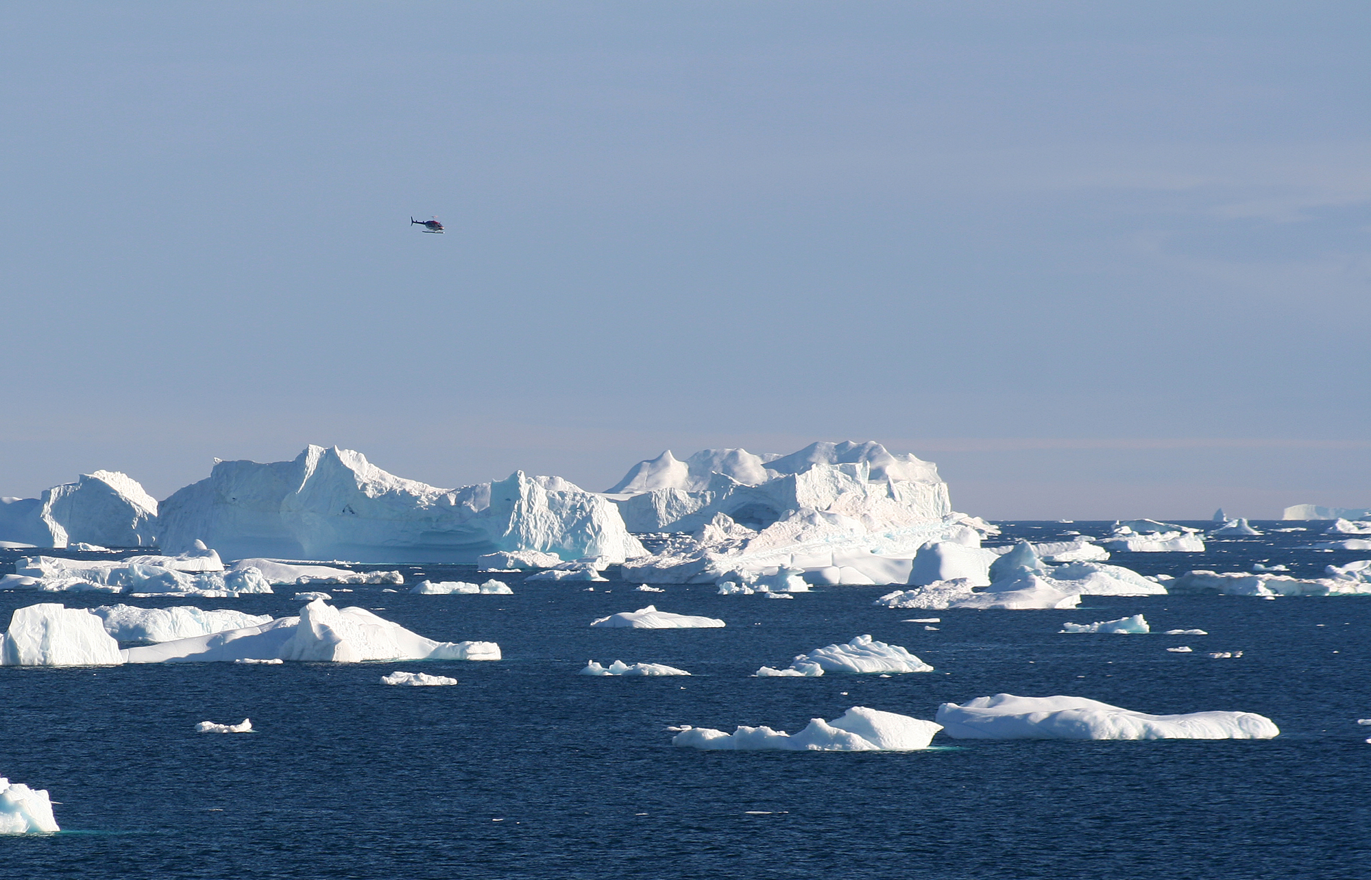 Helicopter flying around the icebergs at Cape York