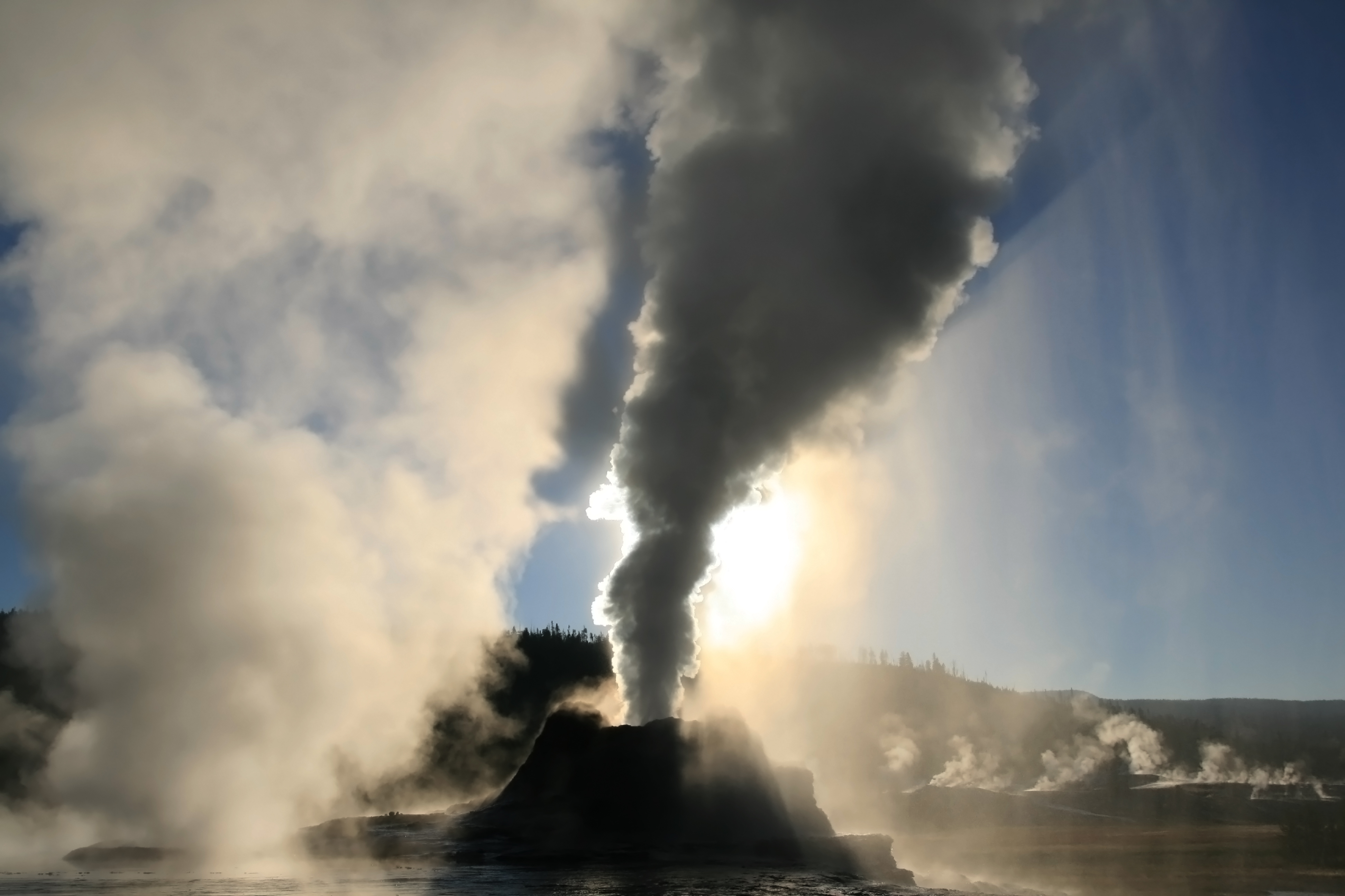 Steam phase eruption of Castle Geyser with crepuscular rays