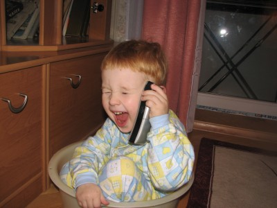 A small funny boy talking over the phone