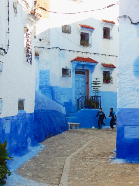 Boys playing soccer on the street in Chefchaouen Morocco