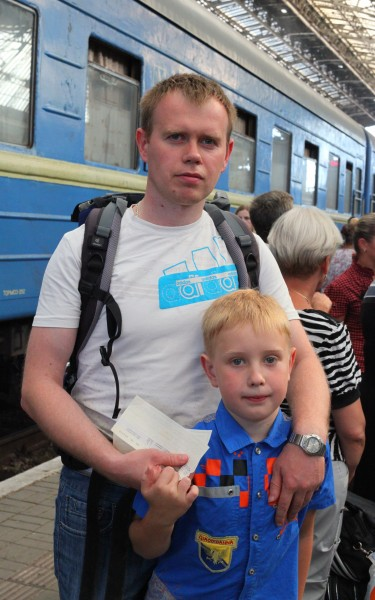 A father and son at a train station