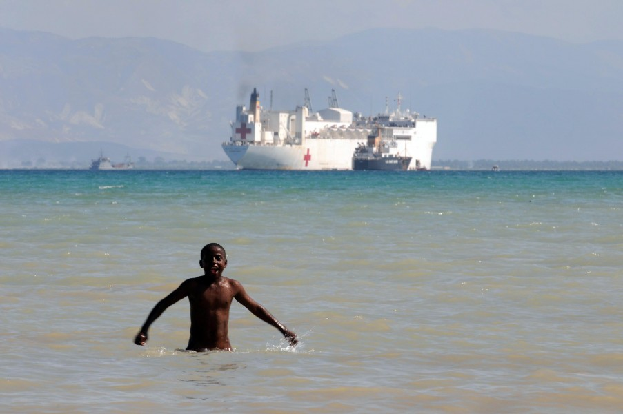 US Navy 100204-N-3592S-202 A Haitian boy plays in the water with the Military Sealift Command hospital ship USNS Comfort (T-AH 20) visible off the coast