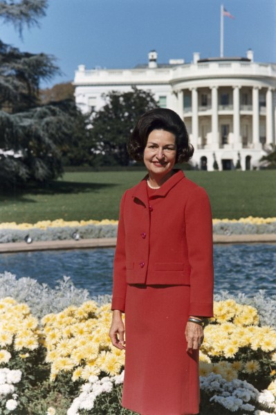 Lady Bird Johnson, photo portrait, standing at rear of White House, color
