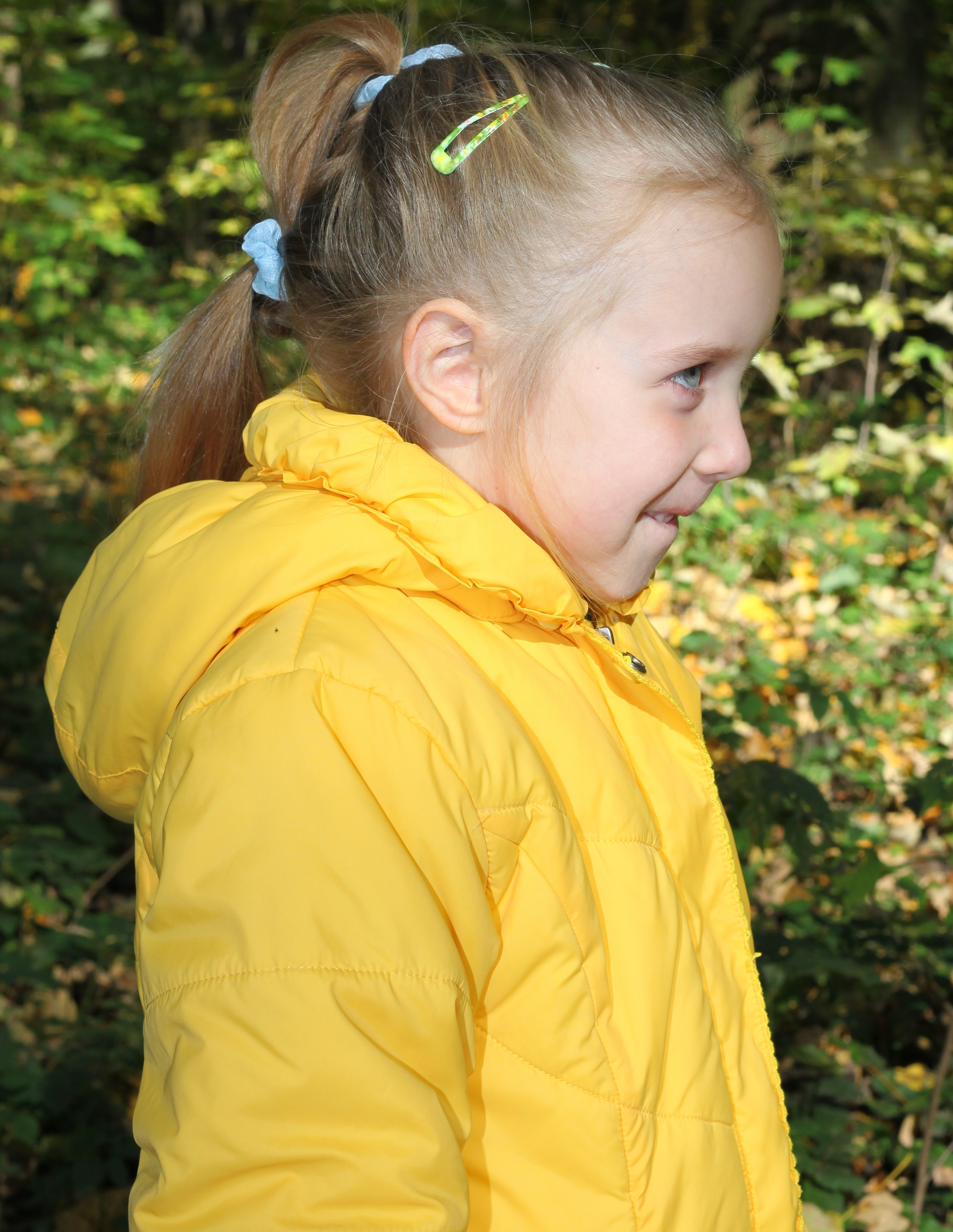 a cute smiling blond Catholic child girl in profile, in a forest, picture 3