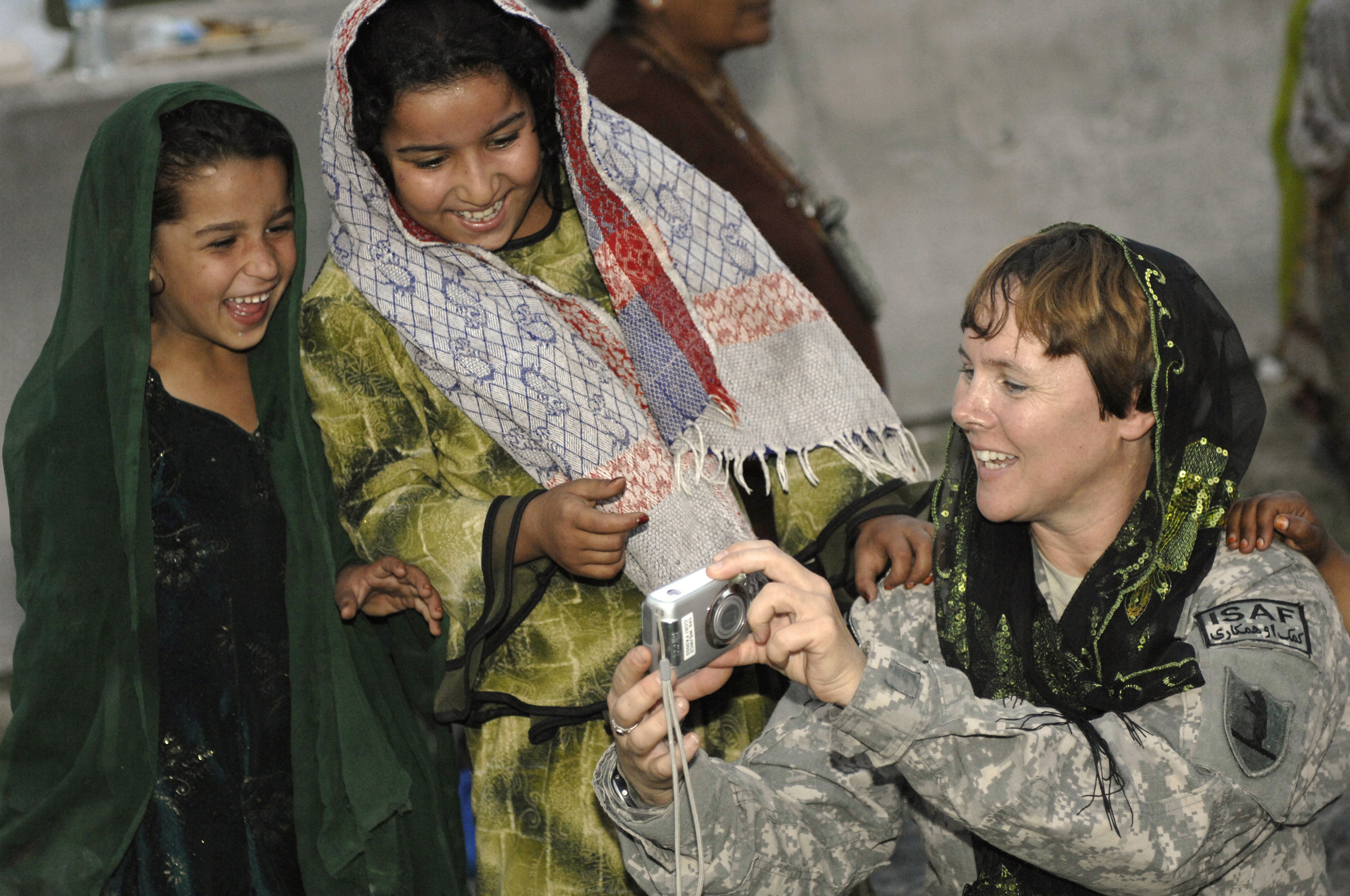Defense.gov News Photo 101009-F-9227G-171 - U.S. Army Capt. Marie Orlando shows Afghan girls photos during their weekly Girl Scout meeting at Forward Operating Base Finley-Shields