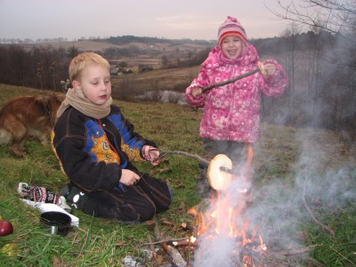 A small boy and a small girl making toasts from bread near fire, picture 2