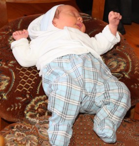 a cute Catholic baby lying on a chair, picture 1