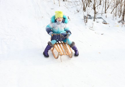 a child girl riding on a sled from a hill