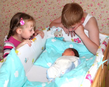 sister and brother happy to meet their newborn brother