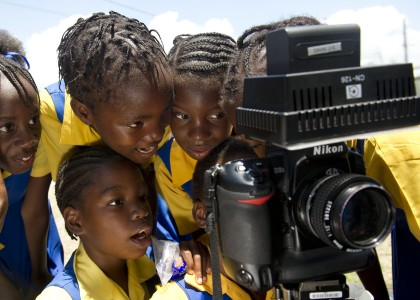 US Navy 110419-N-RM525-454 School children watch a video recording of themselves singing during a Continuing Promise 2011 community service project