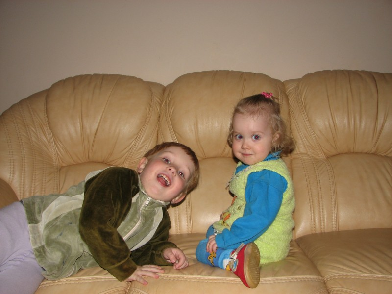 Brother and sister, small children, on a leather sofa