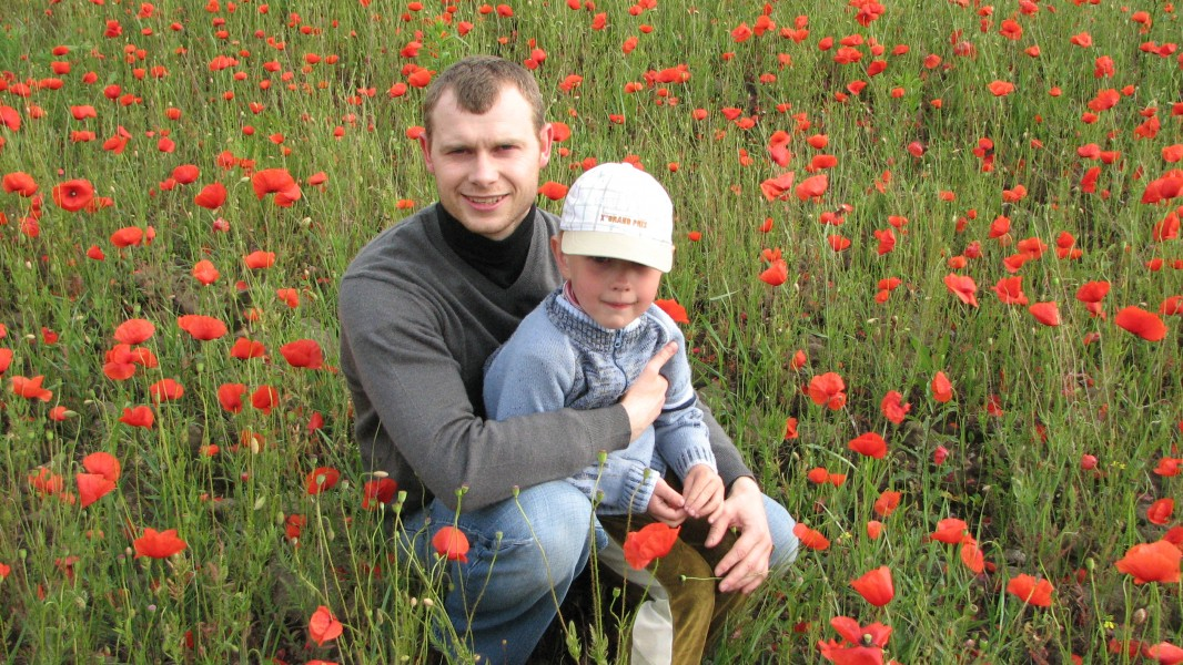 A man with a small boy in a field full of poppies