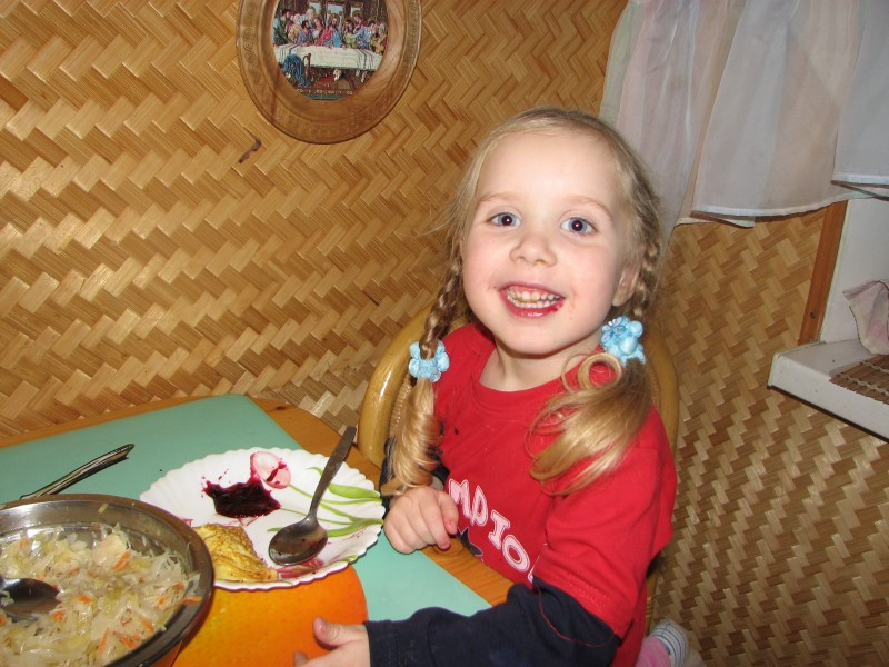A small girl eating at a table