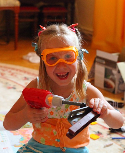 Child girl playing with an electric toy screwdriver