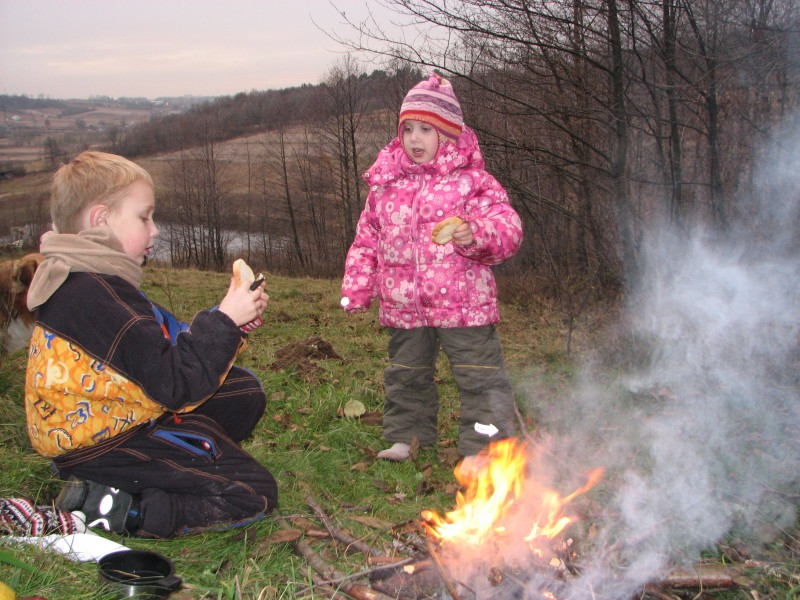 A small boy and a small girl making toasts from bread near fire