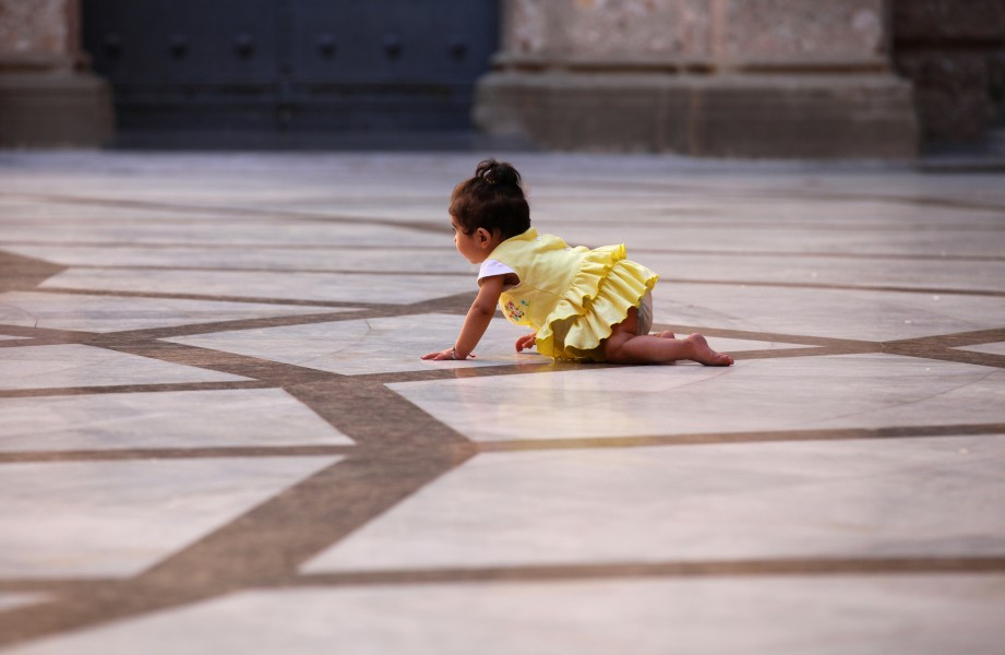 a baby girl crawling in Montserrat sanctuary, Catalonia, Spain, August 2013, photo 1