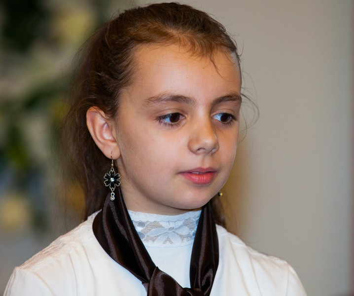 a brunette child girl in a Catholic chapel photographed in November 2013