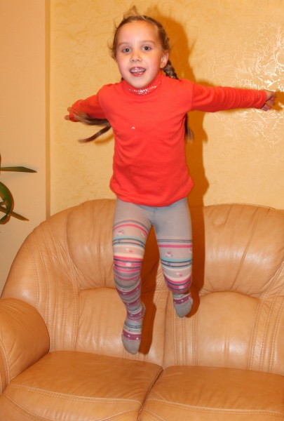 a young cute blond child girl jumping from the sofa