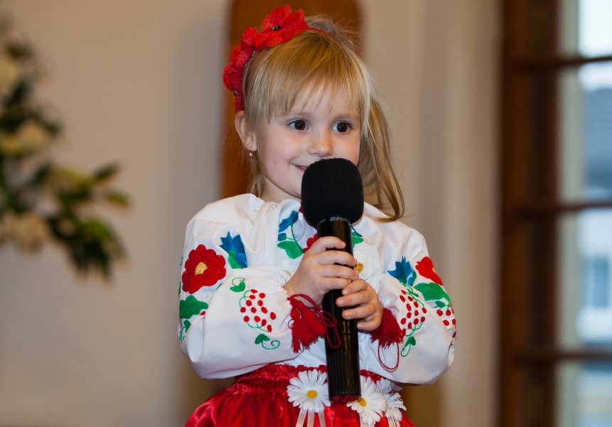 a cute blond child girl with a microphone in a Catholic kindergarten photographed in November 2013, picture 4