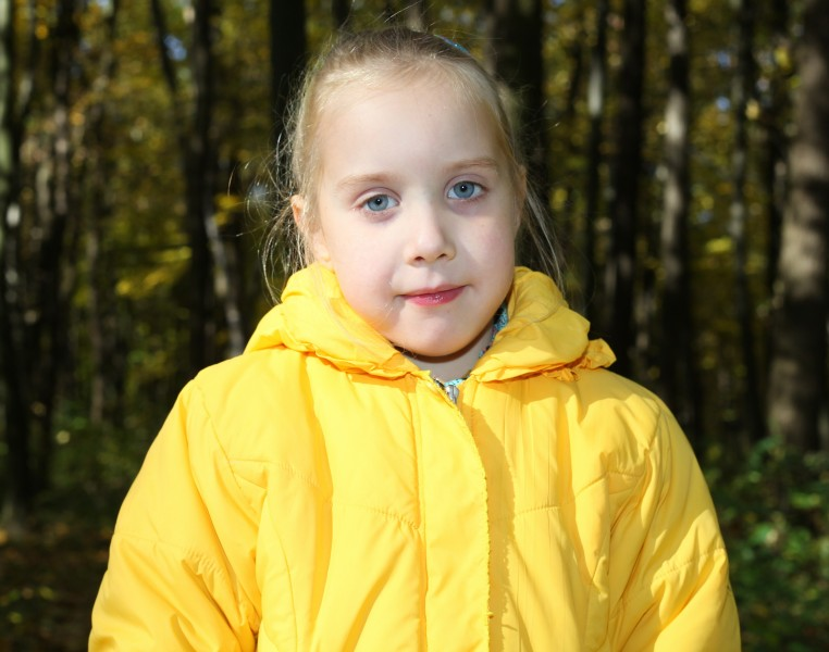 a cute blond Catholic child girl in a forest, picture 1