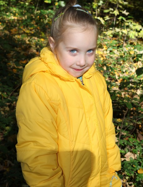 a cute blond Catholic child girl in a forest, picture 2