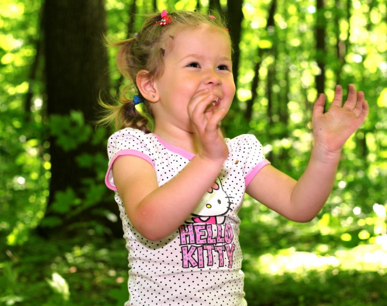 a cute Catholic kid girl in a forest photographed in May 2013, image 2/2