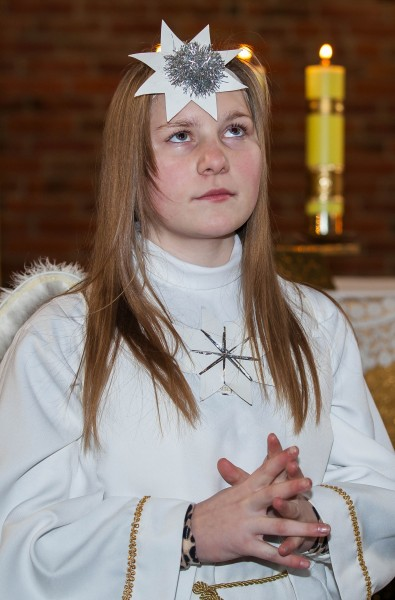 a young Catholic blond girl performing in a play in December 2013, image 1/2