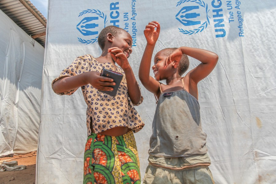 Congolese children holding a bible singing the gospel song in front of the UNHCR tent in Mugombwa refugee camp in Rwanda