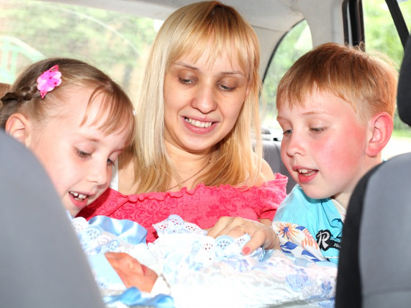 sister, mother and brother taking their newborn baby home