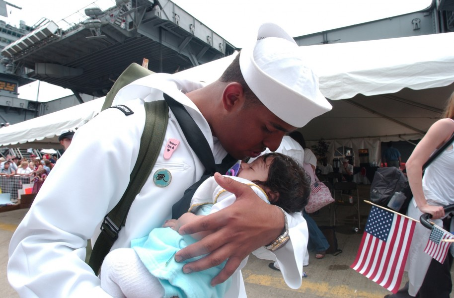 US Navy 030529-N-3642E-001 Airman Andy Nunez kisses his newborn son for the first time after returning from deployment aboard USS Theodore Roosevelt (CVN 71)
