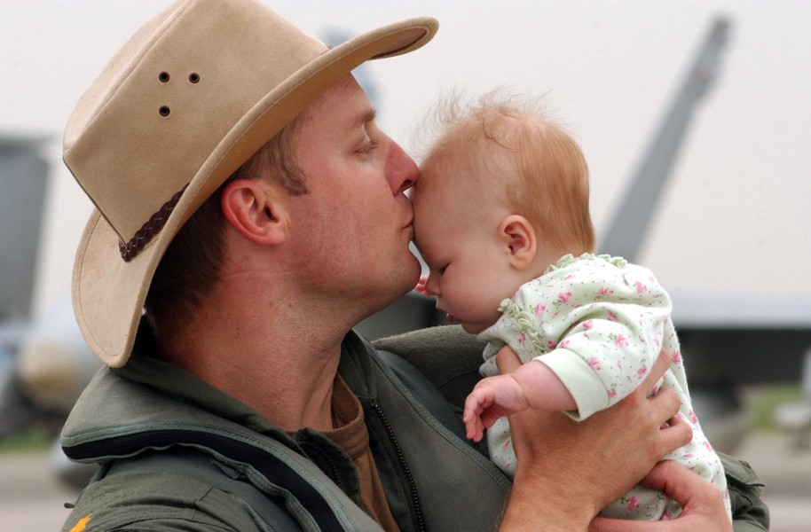 US Navy 040522-N-0435H-001 Lt. Cmdr Sean Cushing kisses his daughter after his return from a deployment