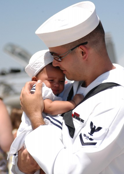US Navy 050731-N-6367N-027 A Sailor hold his child for the first time after returning from a six-month deployment