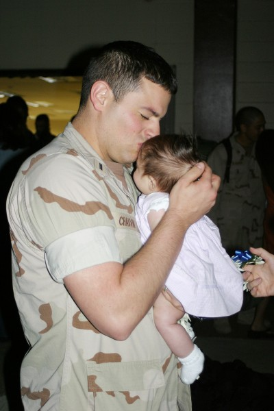 US Navy 060530-N-3207B-023 Lt.J.G. Andrew Chauvin, assigned to the Golden Swordsmen of Patrol Squadron Four Seven (VP-47), kisses his newborn baby for the first time