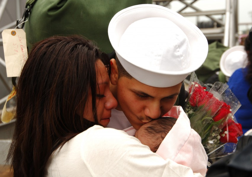 US Navy 061017-N-1831S-158 A Sailor aboard the guided-missile destroyer USS James E. Williams (DDG 95) kisses his child for the first time after returning from deployment