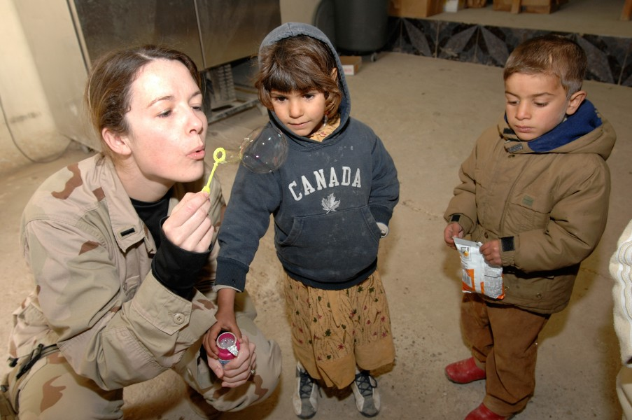 US Navy 070116-N-8218W-030 U.S. Air Force 1st Lt. Lea Ann Fracasso blows bubbles for some Iraqi children at the Civilian Military Operations Center (CMOC) near Baghdad, Iraq