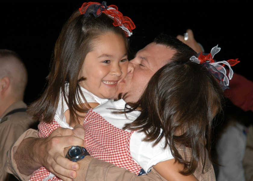 US Navy 070730-N-9860Y-019 Lt. Cmdr. Joe Vandelac, of St. Paul, Minn., kisses his daughters as the Electronic Attack Squadron (VAQ) 134 is welcomed back to Naval Air Station (NAS) Whidbey Island