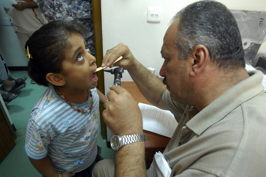 US Navy 080828-N-0292S-005 An Iraqi doctor checks a child's throat during an examination at a free health clinic during a combined medical event for local Iraqi families