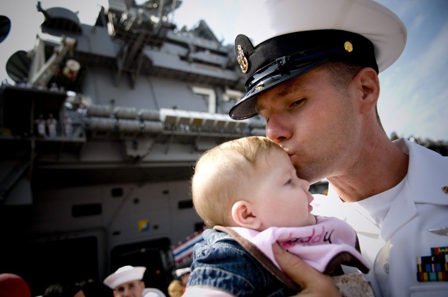 US Navy 080925-N-5549O-211 Chief Aviation Machinist Mate David Lyman gives his newborn daughter Emily a kiss during a ceremony for the arrival of the aircraft carrier USS George Washington (CVN 73) to its new home port in Japan