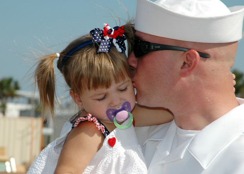 US Navy 081005-N-1522S-021 onar Technician 2nd Class Joseph Meadows kisses his daughter after after his return home aboard the guided-missile frigate USS McInerney (FFG 8) from a six-month deployment