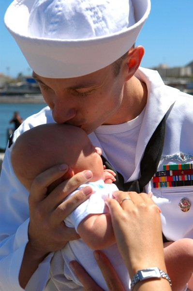 US Navy 090806-N-6031Q-001 A Sailor assigned to the Los Angeles-class attack submarine USS Albuquerque (SSN 706) kisses his baby as he arrives in San Diego