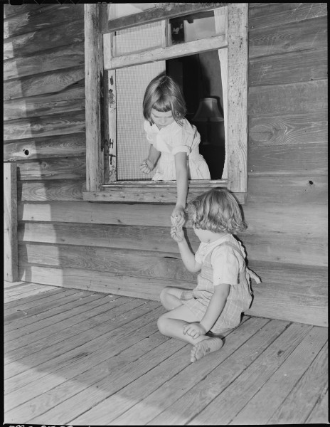 Wanda Lee Sergent hands her sister, Bobbie Jean, an ice cream cone through the window opening from the front porch to... - NARA - 541318
