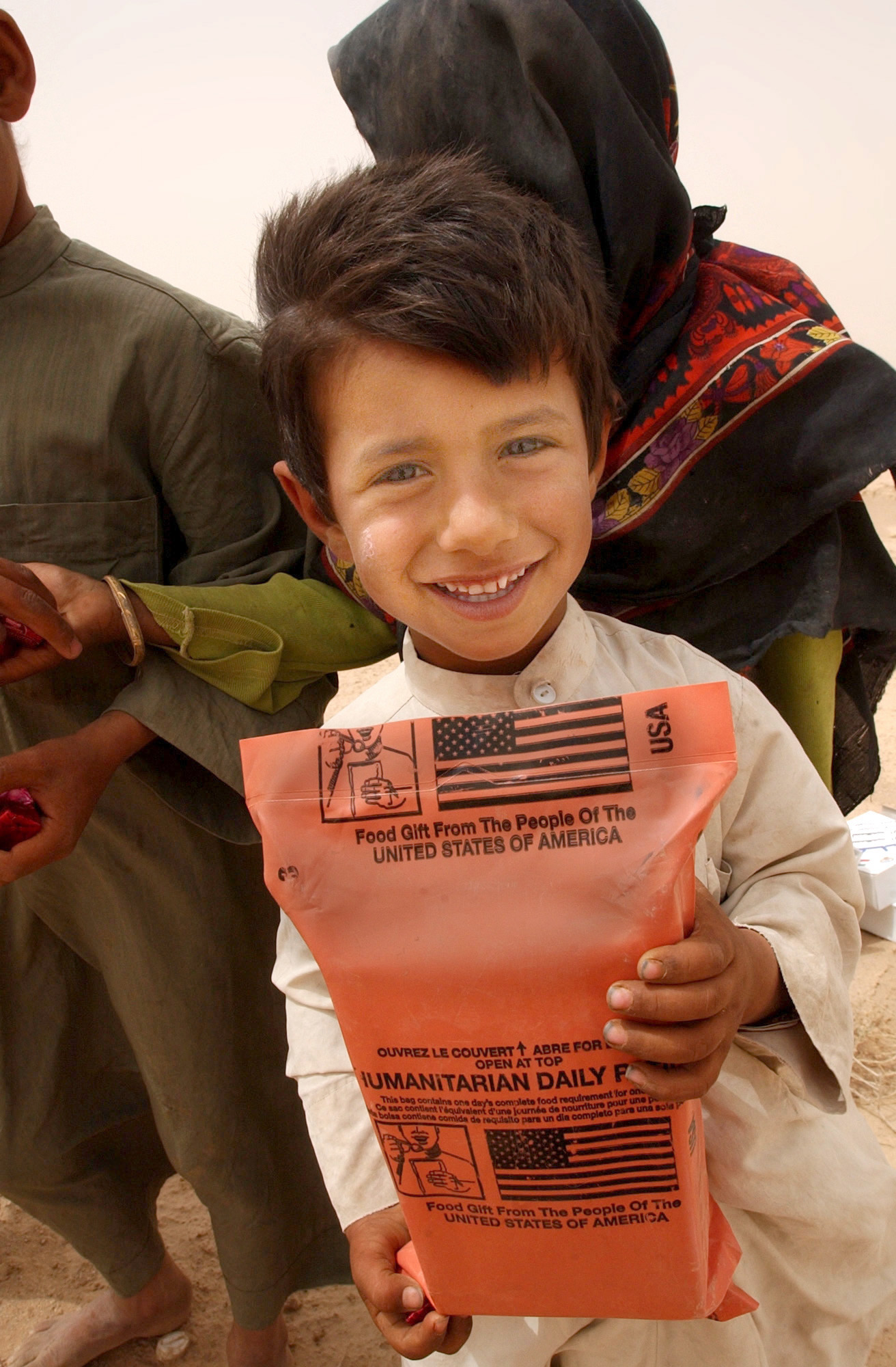 US Navy 030408-N-5362A-001 An Iraqi boy holds a humanitarian food ration given to him by U.S. Army soldiers during an effort to distribute food and water to Iraqi citizens in need